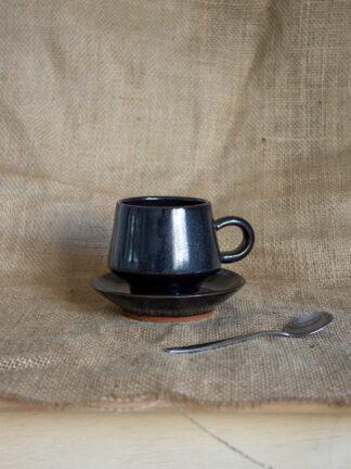 Taza negra con plato de café