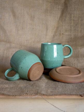 Juego de tazas en verde agua con platos de café negros